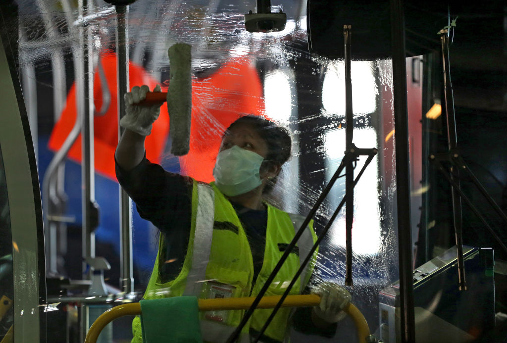 Wearing a protective mask, Alejandra Ceja with S.J. Cleaning Services wipes down the window of a bus at the MBTA Charlestown bus garage during COVID-19 pandemic in Boston on May 15, 2020.