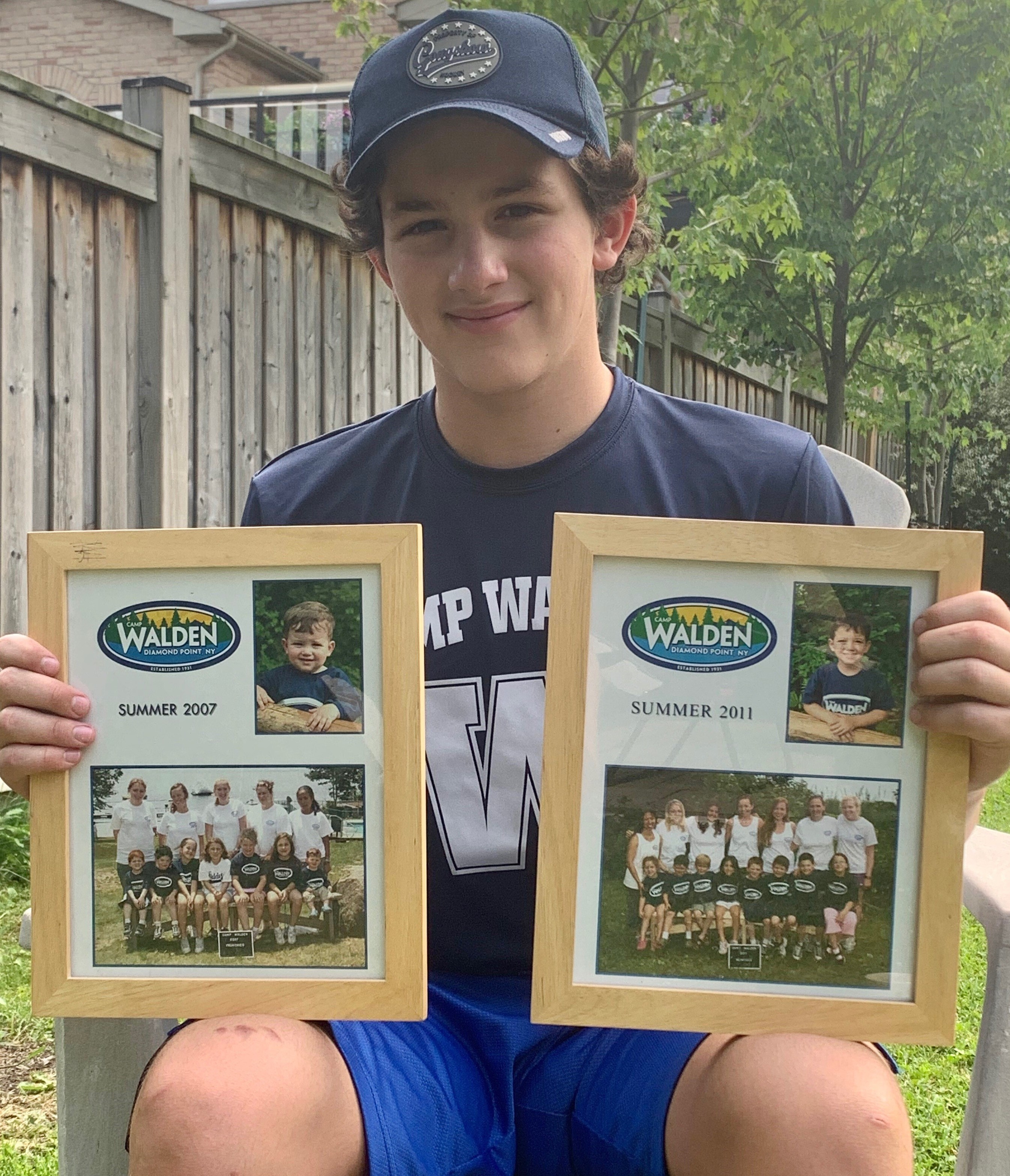 In this June 22, 2020, photo, 14-year-old Rory Sederoff holds framed photos of his previous summers at Camp Walden.