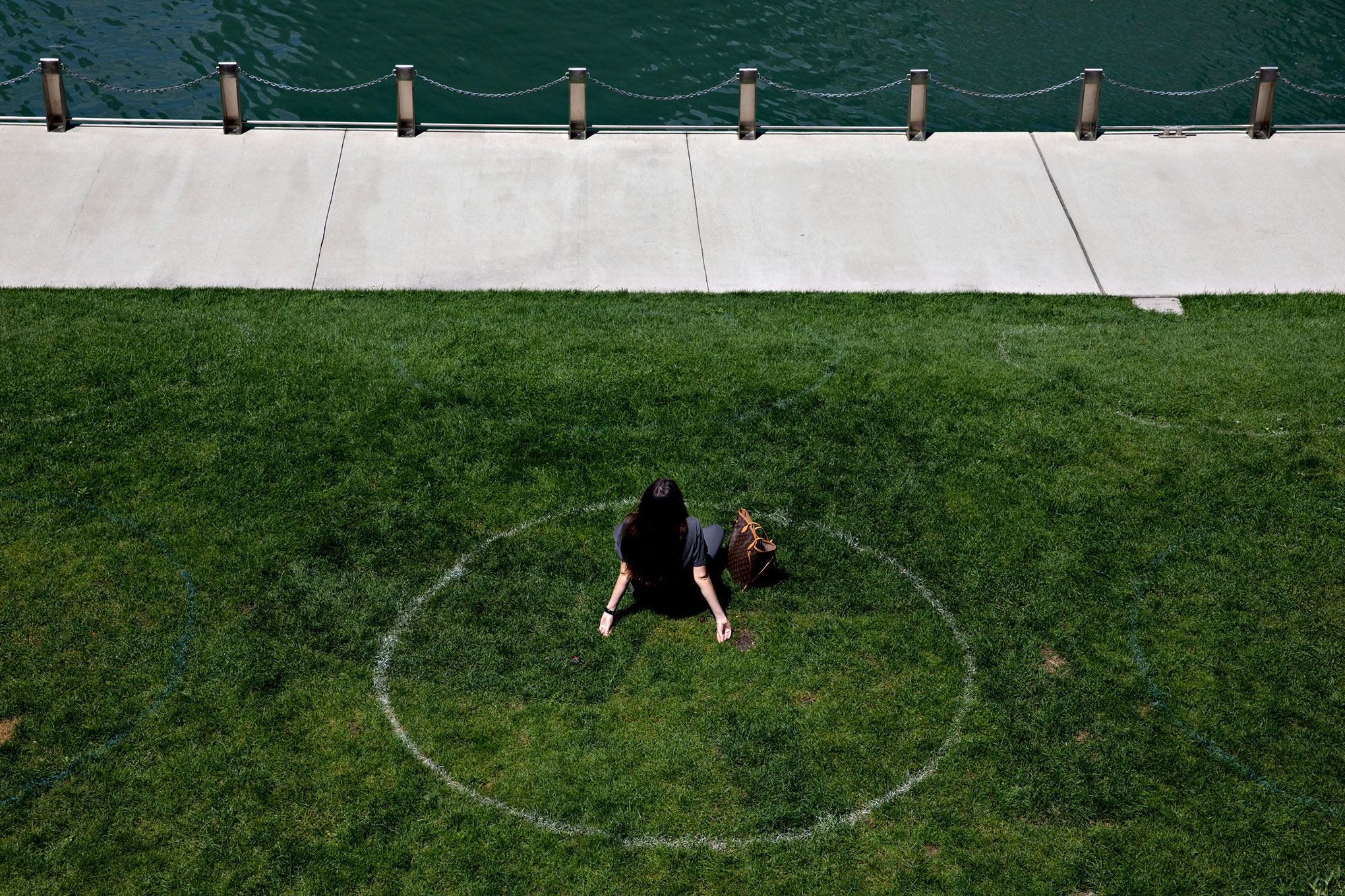 A woman sits in a social distance circle along the Chicago River in Chicago, on Aug. 4, 2020.
